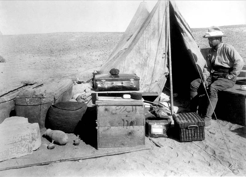 Black and white photograph of a man sitting beside a tent in the desert.