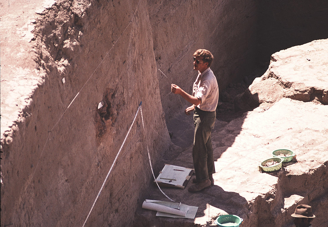 man measuring earth wall in pit