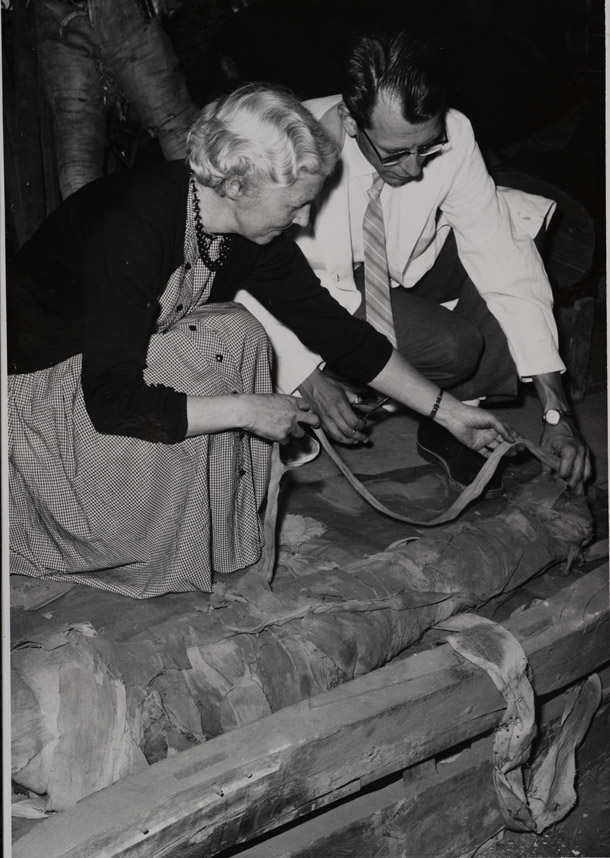 man and woman unwrapping a mummy