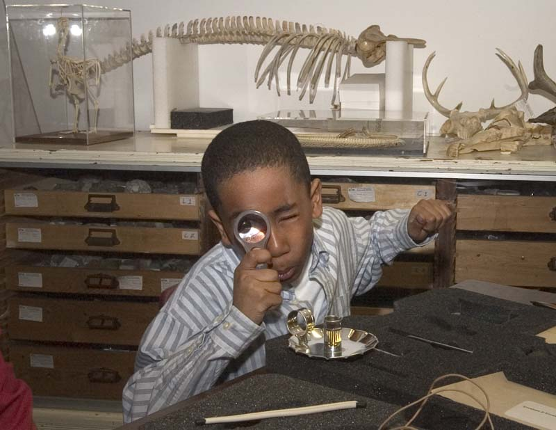 child with magnifying glass in gallery