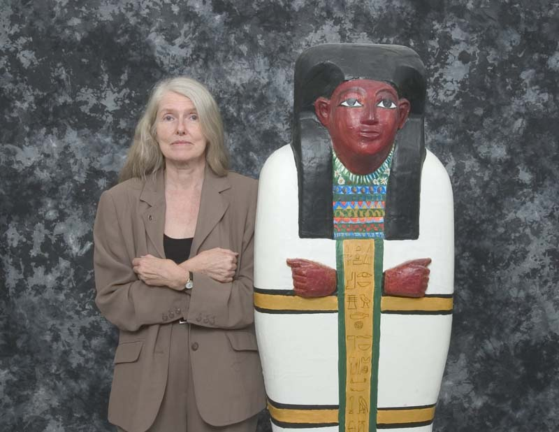woman stands beside mummy case