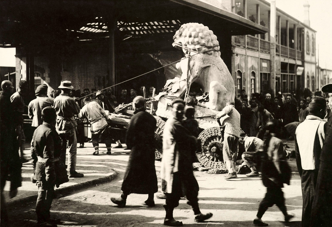 stone lion being transported in street