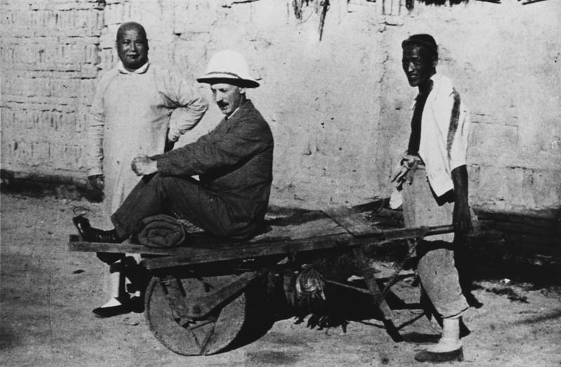 man sitting on wheelbarrow with two porters