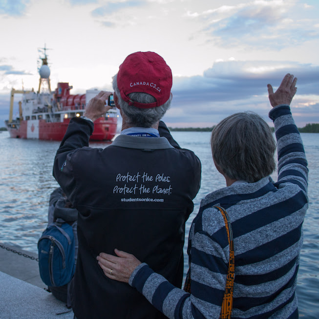 Two people wave farewell to a departing Polar Prince boat from shore at the Canada C3 launch on June 1st in Toronto. Photo credit: Mary Paquet