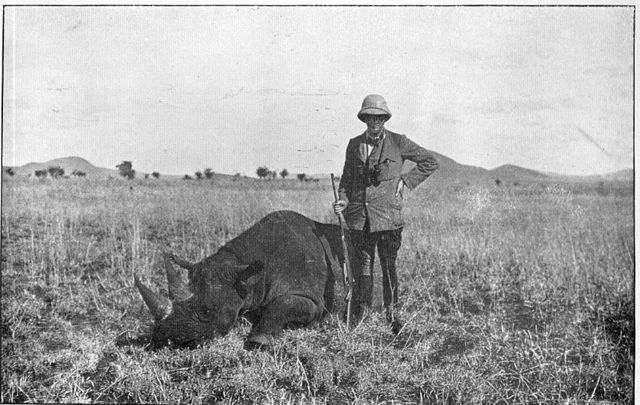 A hunter stand over the body of a white rhino in an old, black & white photograph