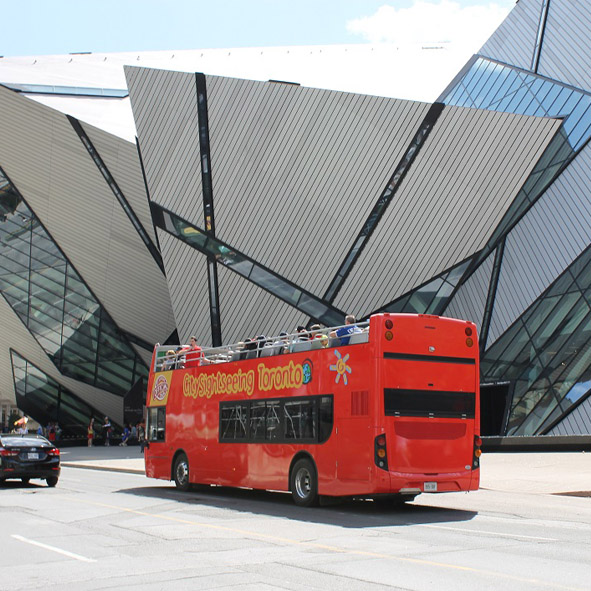 Double-decker bus passing by the Royal Ontario Museum.