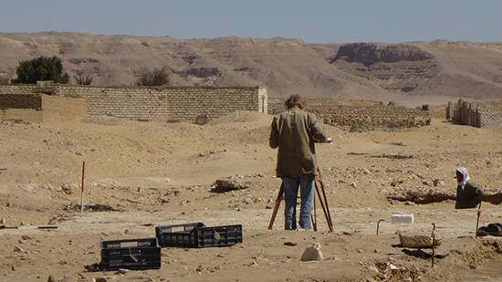 Man standing behind a tripod looking over the archaeological site in Egypt.