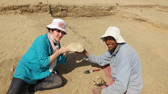 Laura and Mustafa crouch in the sand holding an artifact they have discovered.