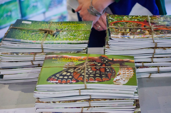 Stacks of Toronto Biodiversity books sit on a table bound with twine
