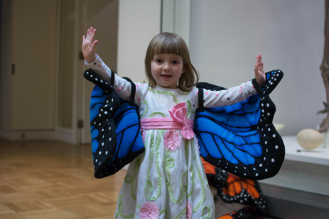 A young girl poses with butterfly wings in the Schad Gallery. Photo by Fatima Ali