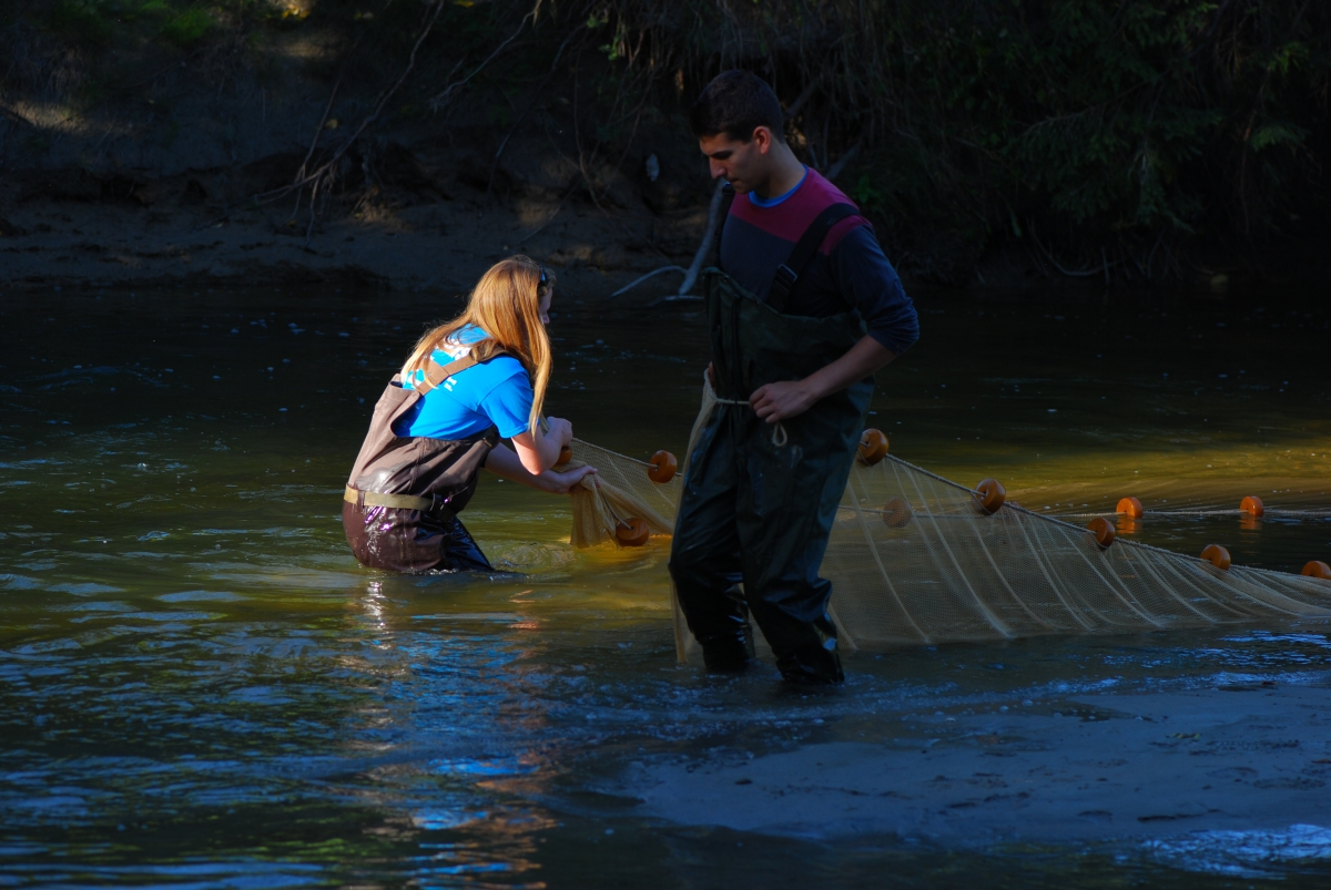 A woman and a man wearing hip waders with a net stand in a river