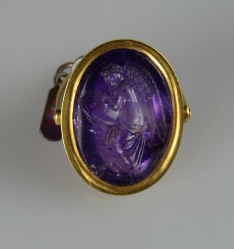 Front face of ring displaying engraving in purple stone.