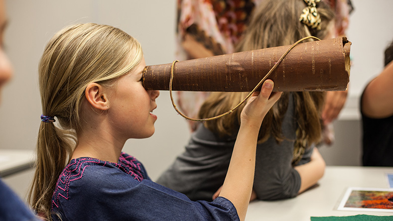 Girl looking through a telescope