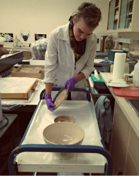Emily Ricketts. Holding a Portneuf Spongeware plate in Conservation Lab. Photo by Jaime Clifton-Ross