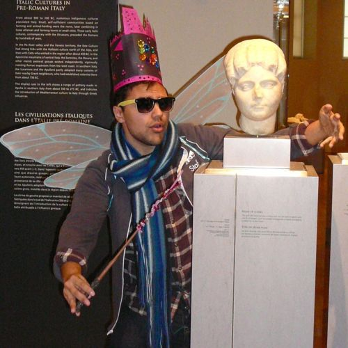 Kiron Mukherjee dressed as a fairy, posing with a roman bust on display in the Eaton Gallery of Rome.
