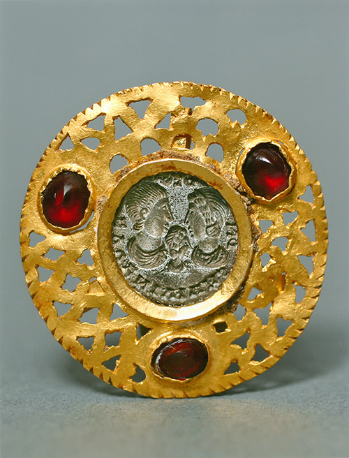 A gold pendant flanked with red gems with a silver inset depicting three human figures.