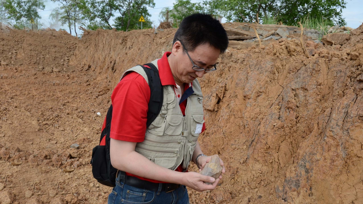 Dr. Chen Shen picking up the hand axe from a site that runs through the newly built highway