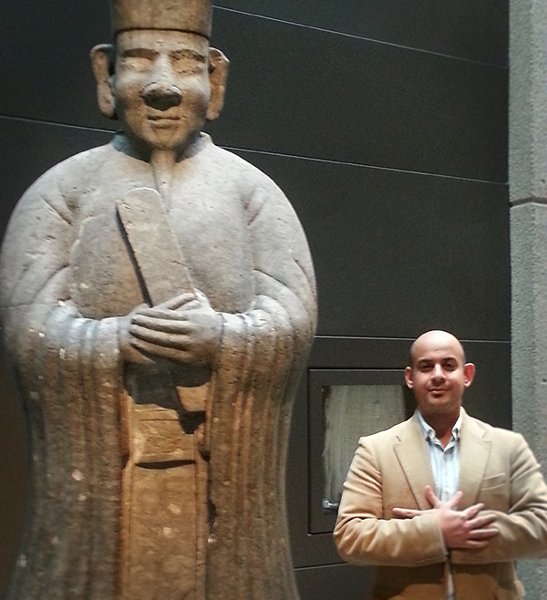 Visitors to the ROM pose beside a lime stone statues stand in the Gallery of China on Level 1