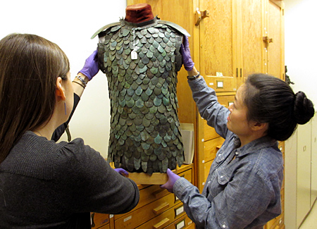 Two women carefully adjust an armour vest on a stand.