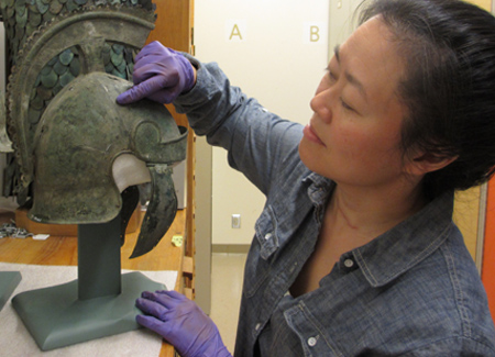 A woman examines a helmet inside the ROM's storage rooms.