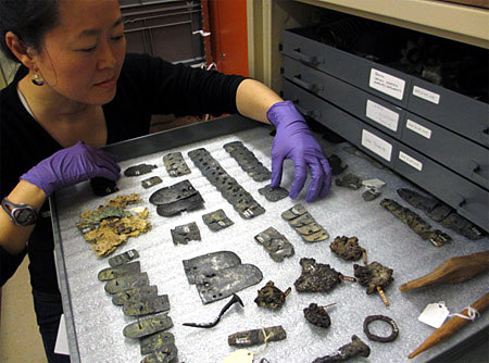 A woman arranges objects inside a metal drawer in the ROM's storage room.