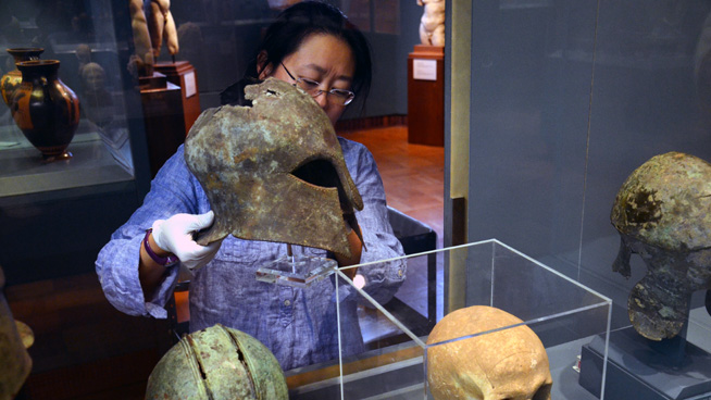 Kay Sunahara of the ROM's Greek & Roman section removing a Corinthian helmet from the gallery for study.