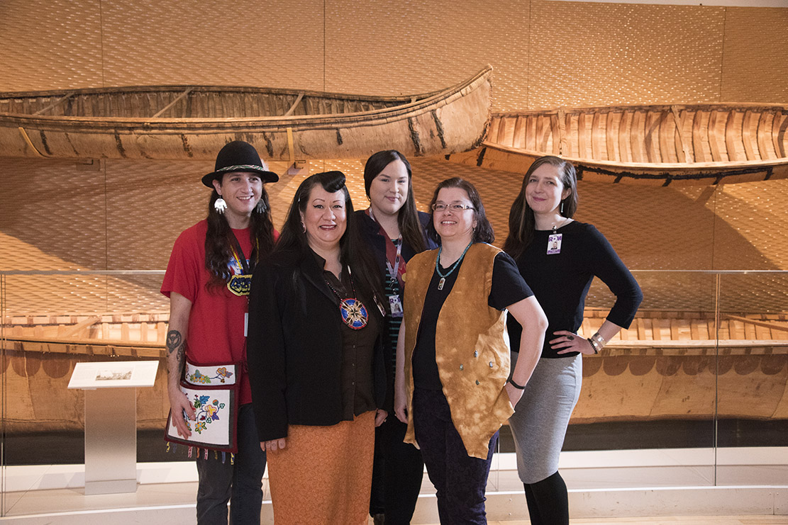 Five Indigenous men and women standing in front of canoes in the First Peoples Gallery