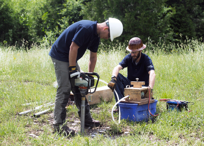 Two men with hard hats and drilling equipment in grassy field drilling into ground.