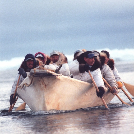 Historic coloured photograph of Inuit hunters in a hunting boat on the water
