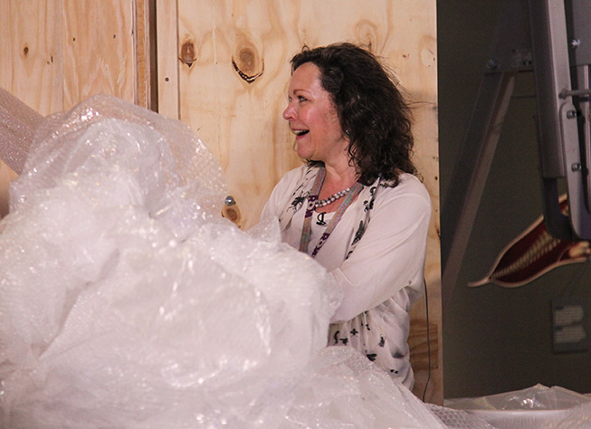 The final reveal: Jacqui watches as the blue whale heart is unpacked and installed into the exhibition. Photo by Fennella Hood