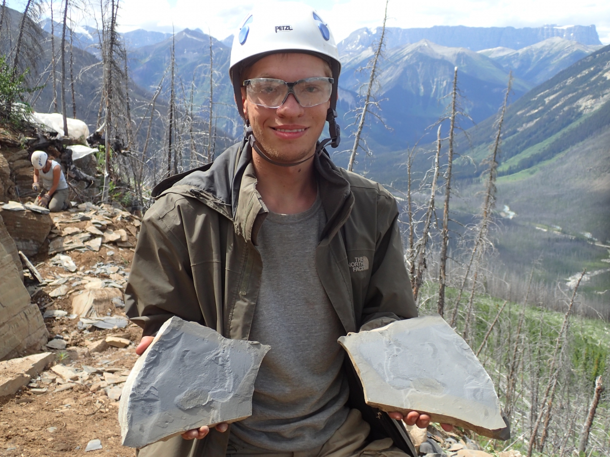 Man with goggles and a white helmet stands on a rocky mountaintop holding two pieces of fossilized rock. Bare trees and rocks are behind him, and a co-worker drills into a rock a few feet behind, and in the background is a range of sloping green mountains.