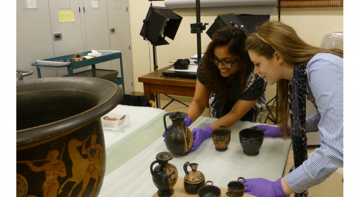 Natasha Ali & Lindsay Britton examining ancient artifacts