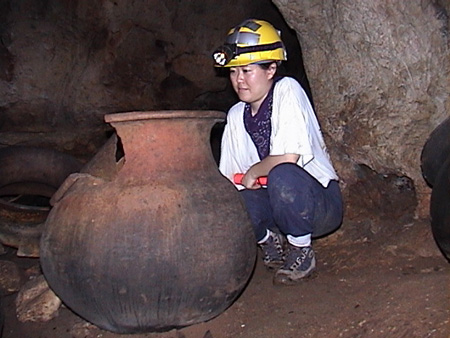 Kay crouches beside a large pot inside a dark cave.