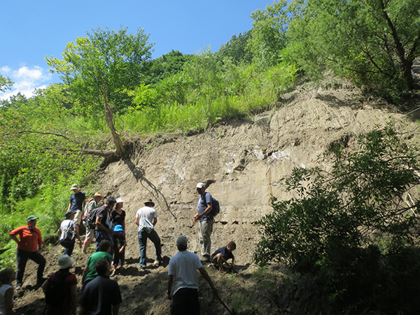 Group stands in fron of an exposed rock wall.