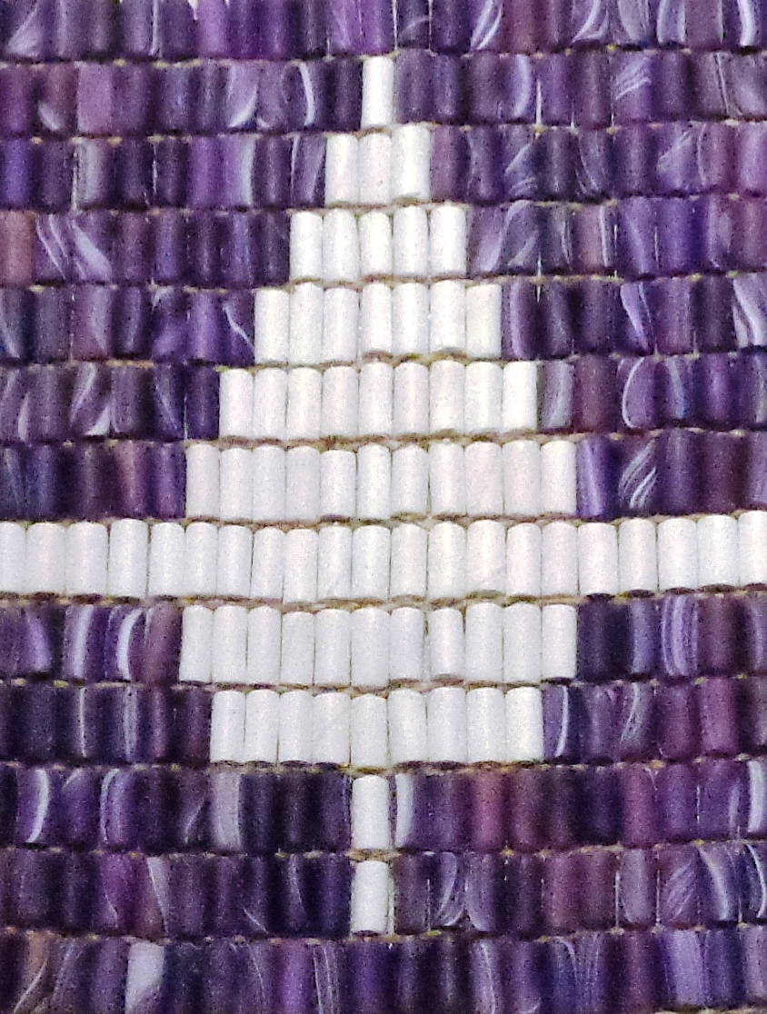 a close-up of a belt made of purple and white beads
