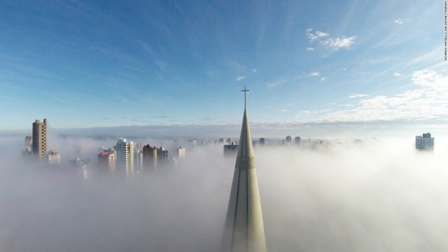 """Above the mist,"" taken in Maringa, Brazil, was the most-liked photo in this year's CNN 2015 Drone Aerial Photography Contest. The photo is a view of the Brazillian city from above a blanket of fog, showing the tips of skyscrapers poking through the low-lying cloud, and the vast blue sky above. Photo by Ricardo Matiello."