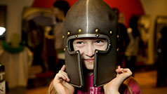 Families play dress-up in the ROM's hands-on galleries. Girl wearing a medieval helmet from a suite of armour.