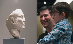 An adult and child look at an artifact from the Eaton Gallery of Rome