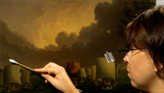 A conservator restoring a historic painting in the ROM's collection.