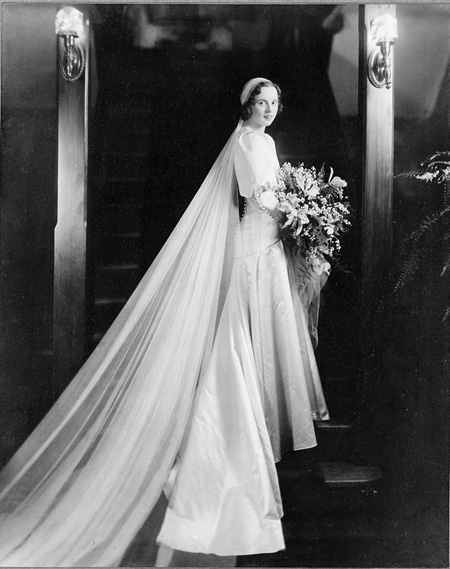 Portrait of bride in wedding gown standing on stairs.