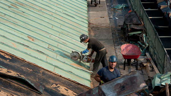 Man cutting copper roof