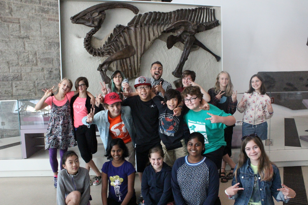 A group of happy campers in front of the Museum's famous Parasaurolophus.