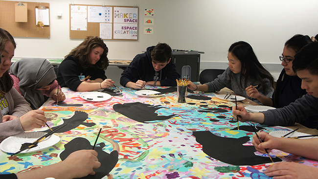 A group of Youth Cabinet members paint at a table onto canvas.