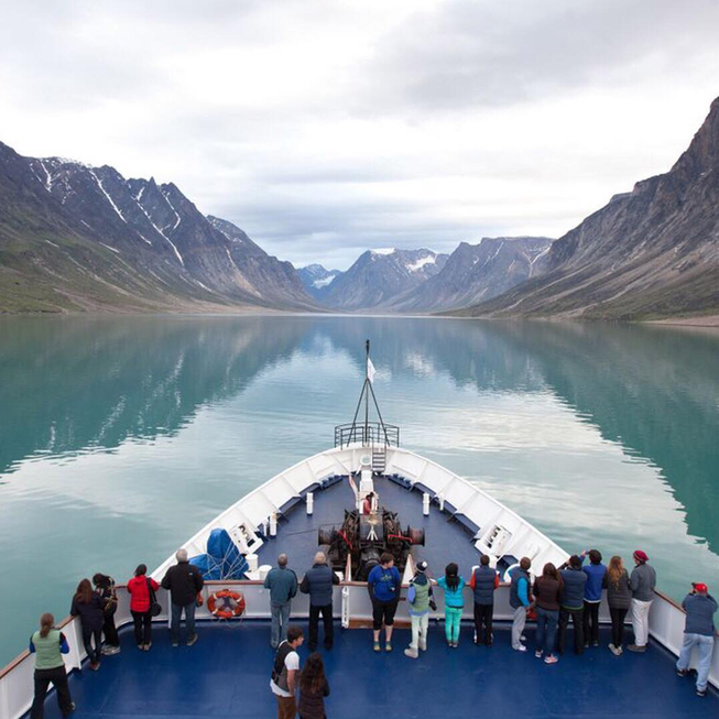 A view from the bow of the C3 Expedition ship of water bordered on both left and right by walls of rock in the Canadian Arctic. Photo Credit Lee Narraway