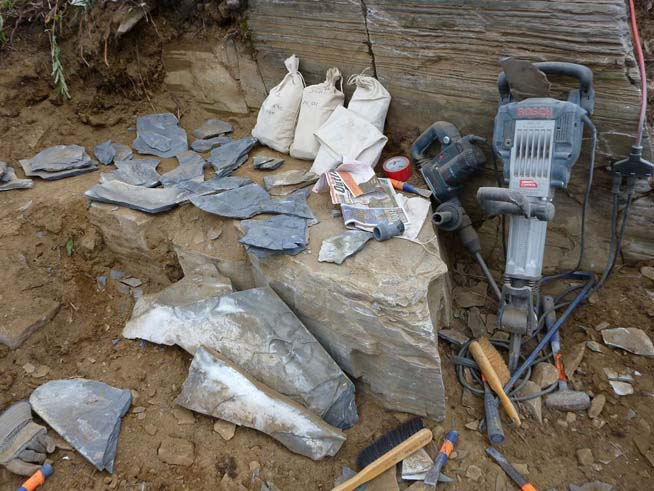 Field equipment including jackhammers, and fossils being labeled and wrapped before packing.