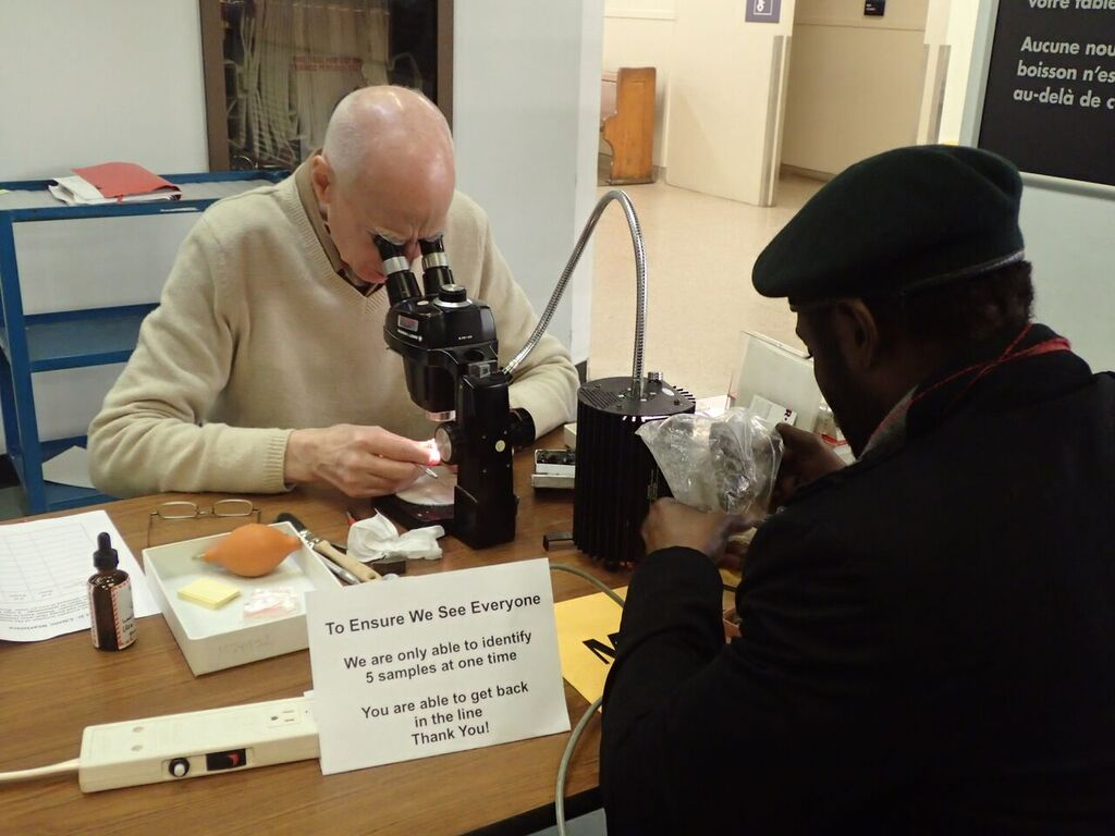 A bald man with a ring of white hair in a beige sweater studies an item under a microscope while another man in a black coat and beret is across the table, looking at another item inside a Ziploc bag