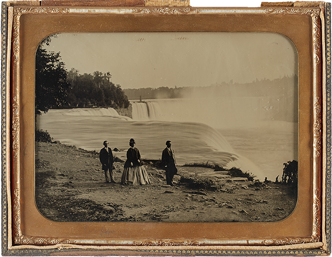 Framed black and white image of three tourists walking beside Niagara Falls
