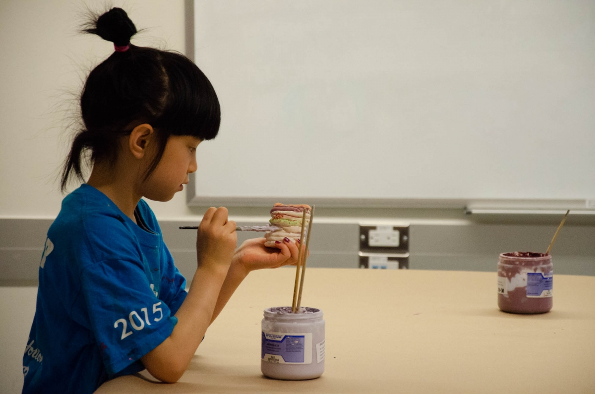 A student paints her ceramic pot in class. Image: Michael Berger