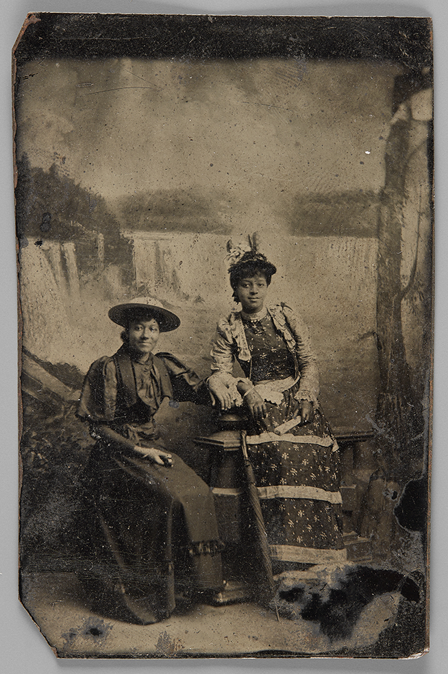 Black and white photo of two women sitting in front of Niagara Falls