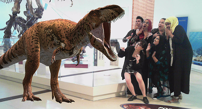 Photo of the youth cabinet next to a T. rex!